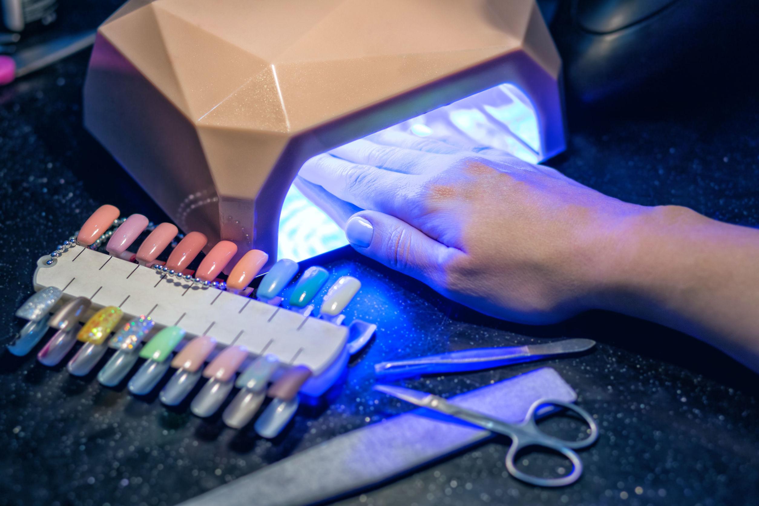 Foto de mão feminina dentro de uma cabine de led, que está ligada, ao lado de unhas postiças coloridas, pinça, lixa e tesourinha para unhas.