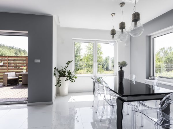 Sala de jantar grande e bem iluminada com uma mesa preta e algumas cadeiras transparentes em volta dela. Pelas janelas e porta podemos observar paisagens naturais e um dia ensolarado.