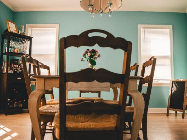 Foto de uma mesa de madeira com seis cadeiras também de madeira, em uma sala de jantar de paredes verdes, um mini bar e teto e janelas brancas.
