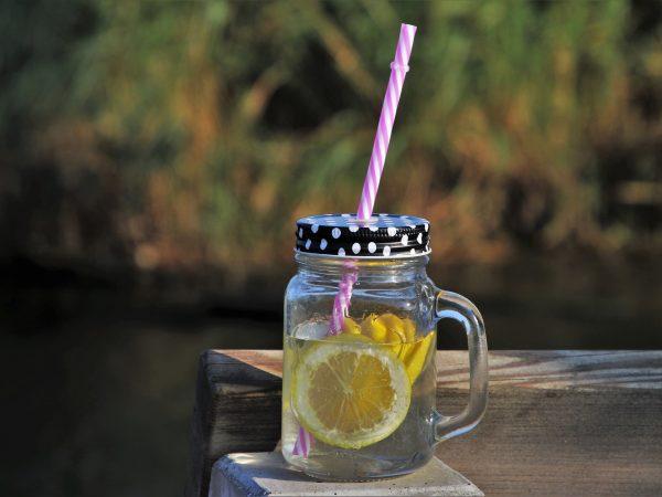 Imagem de caneca de vidro com tampa e canudinho com suco de limão