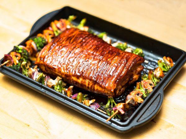 Imagem de carne assada e espetinhos de legumes em chapa de ferro fundido