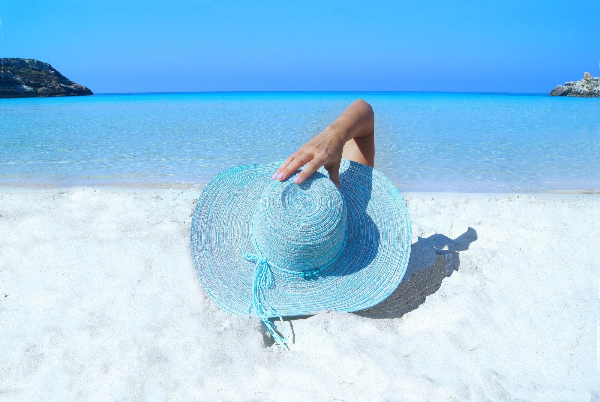 Foto de uma pessoa deitada na areia branca da praia, de forma a só aparecer seu chapéu de praia azul claro e sua mão, segurando o chapéu. AO fundo, o céu e o mar bem azuis.