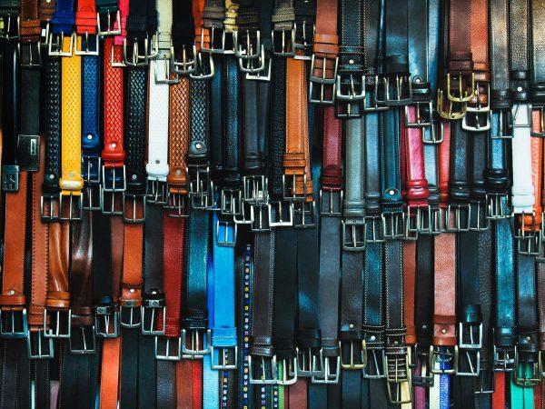 Foto de inúmeros cintos coloridos pendurados.