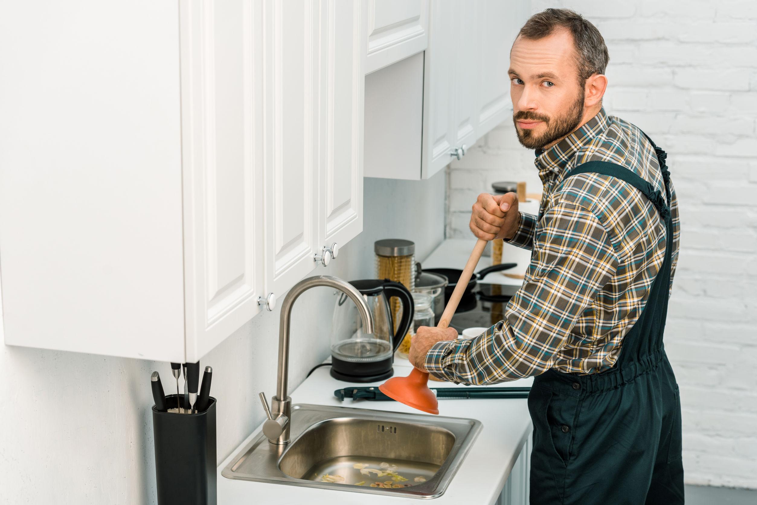 Um homem que coloca um desentupidor em cima de uma pia em uma cozinha