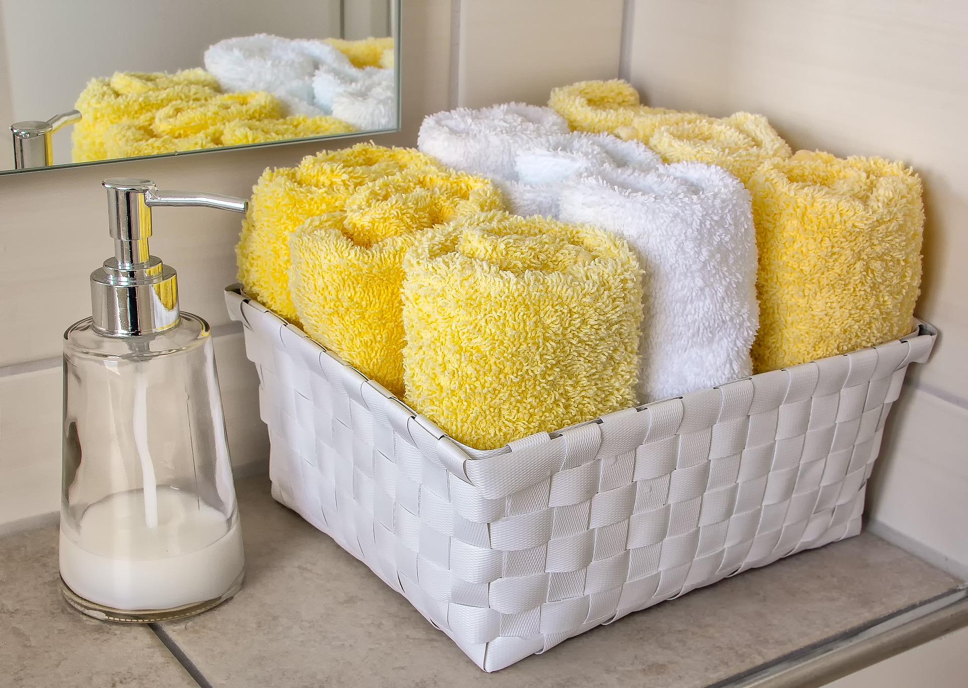 da imagem destacada: Dispensador de sabonete líquido e kit de toalhas coloridas na pia do banheiro.