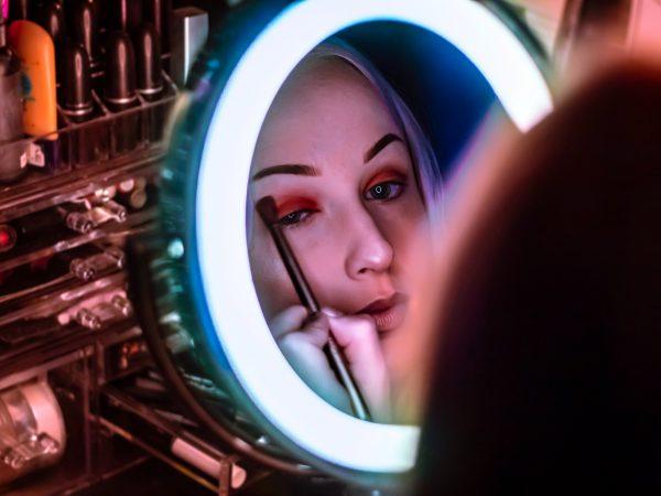 Moça se maquiando em espelho com luz de bancada