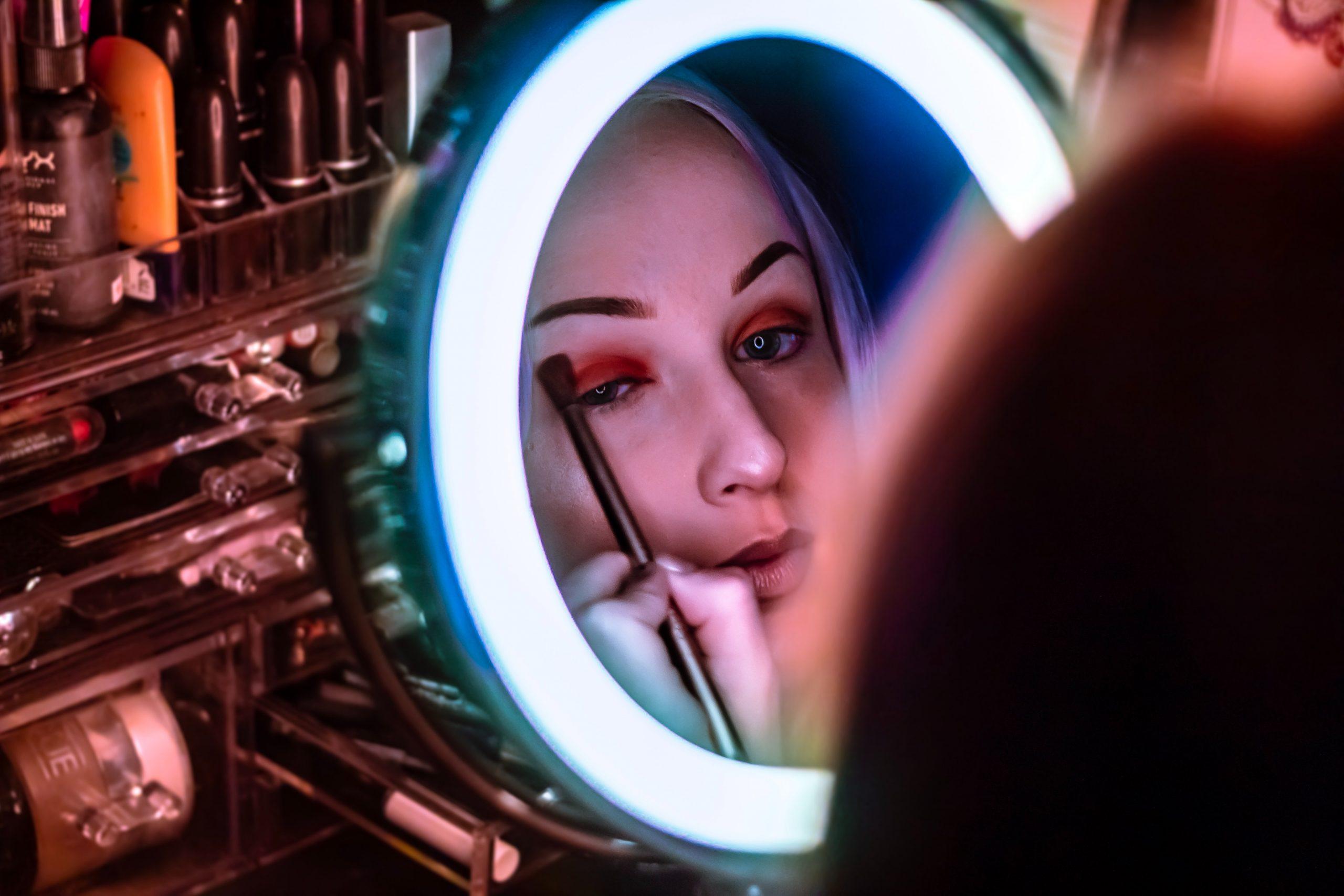 Foto de uma mulher passando maquiagem nos olhos, em frente a um espelho redondo, com luz de led.