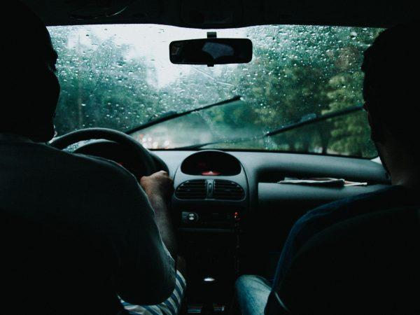 Foto tirada do banco de trás de um carro, que mostra toda a parte da frente do carro, incluindo o banco do motorista e do passageiro, que estão ocupados. Do lado de fora chove e o limpador de para-brisa está ligado.