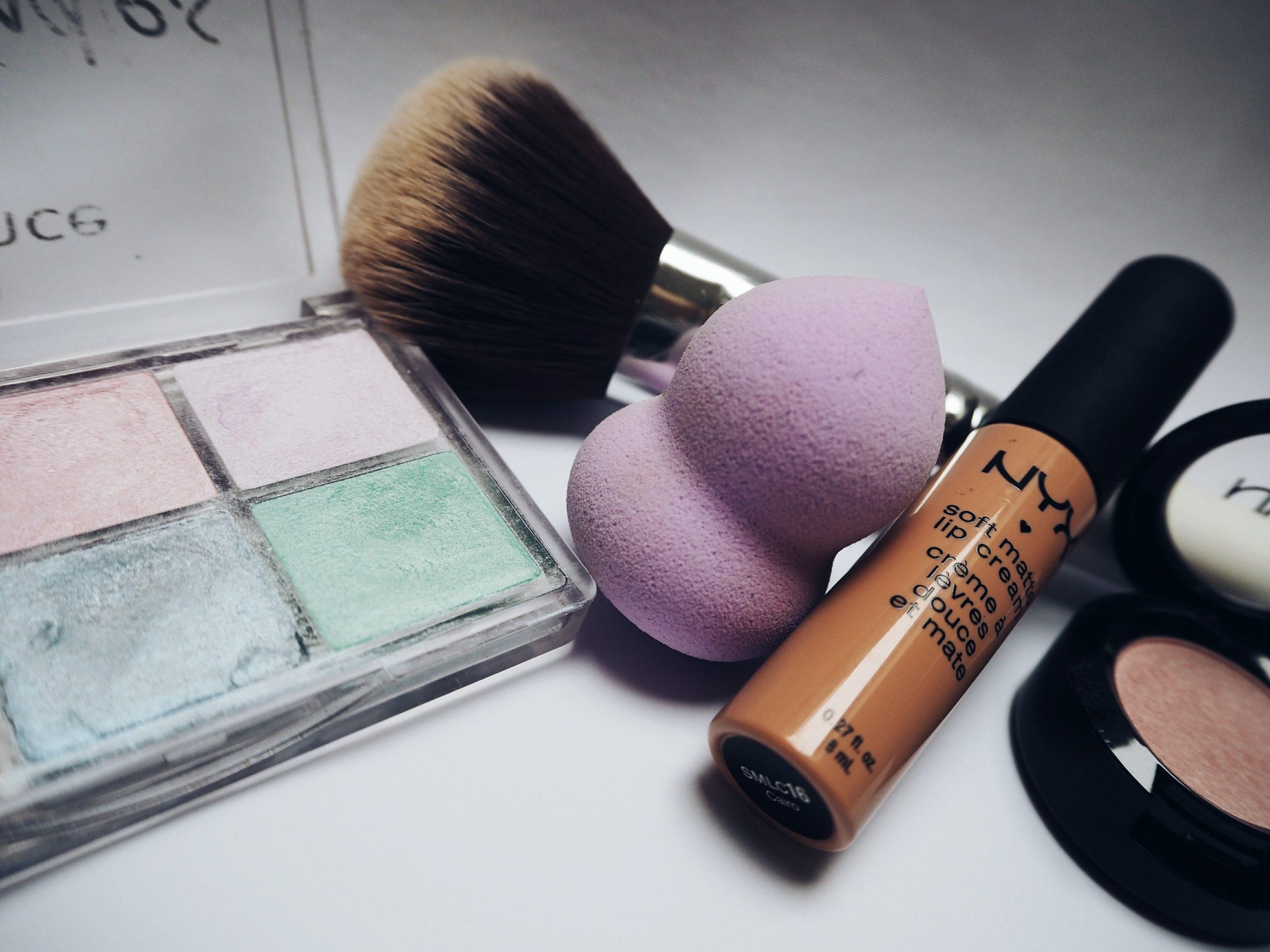 Foto uma esponja de maquiagem roxa, ao lado de um pincel, uma paleta de sombras e um blush.