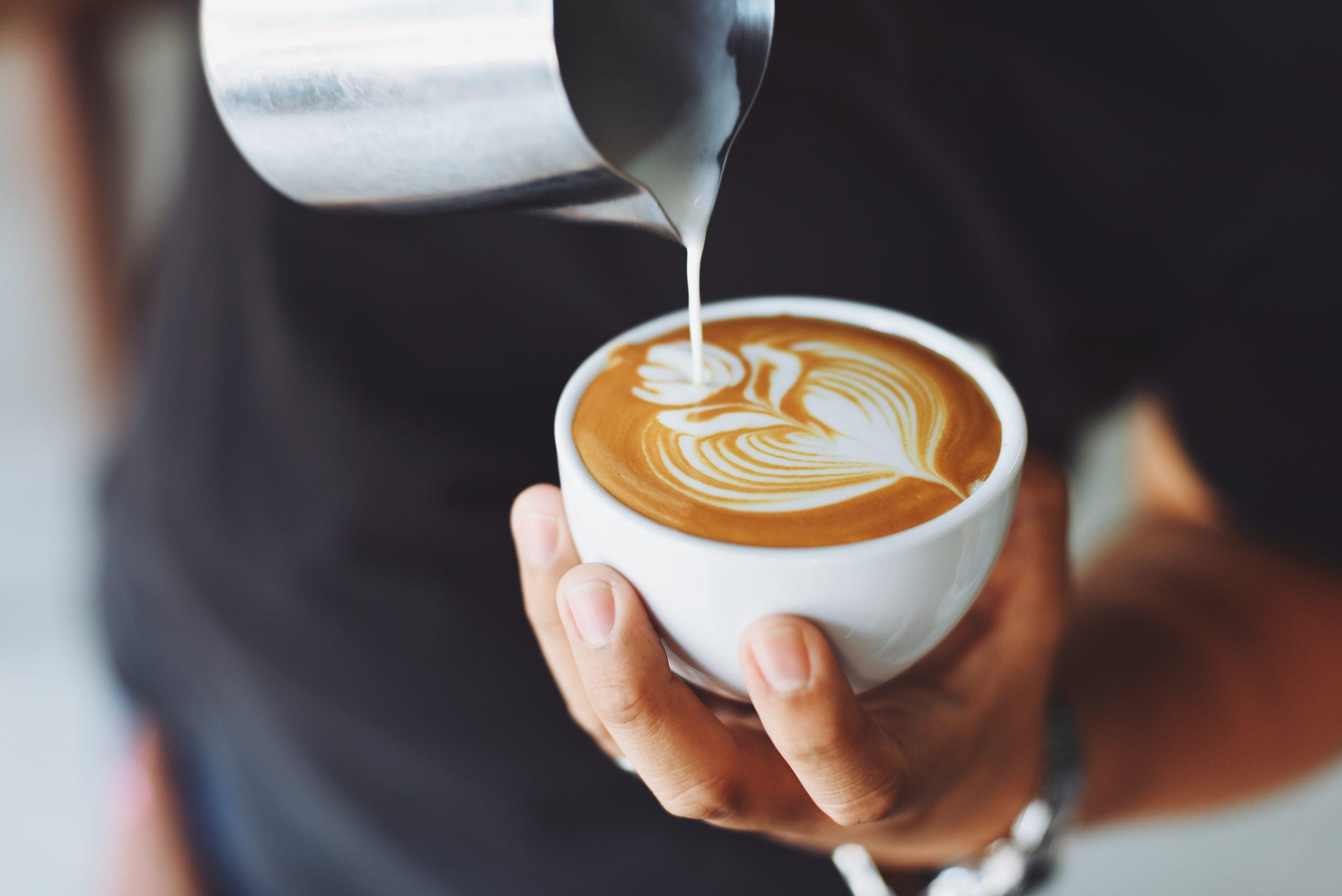 Imagem de pessoa usando um fervedor para servir leite em xícara de café