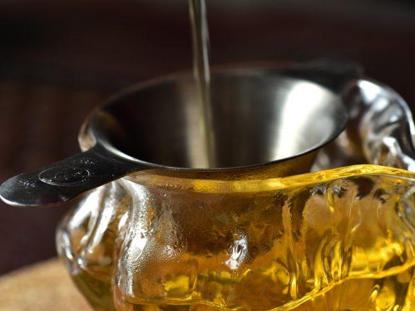 Imagem de pessoa preparando chá utilizando um funil metálico