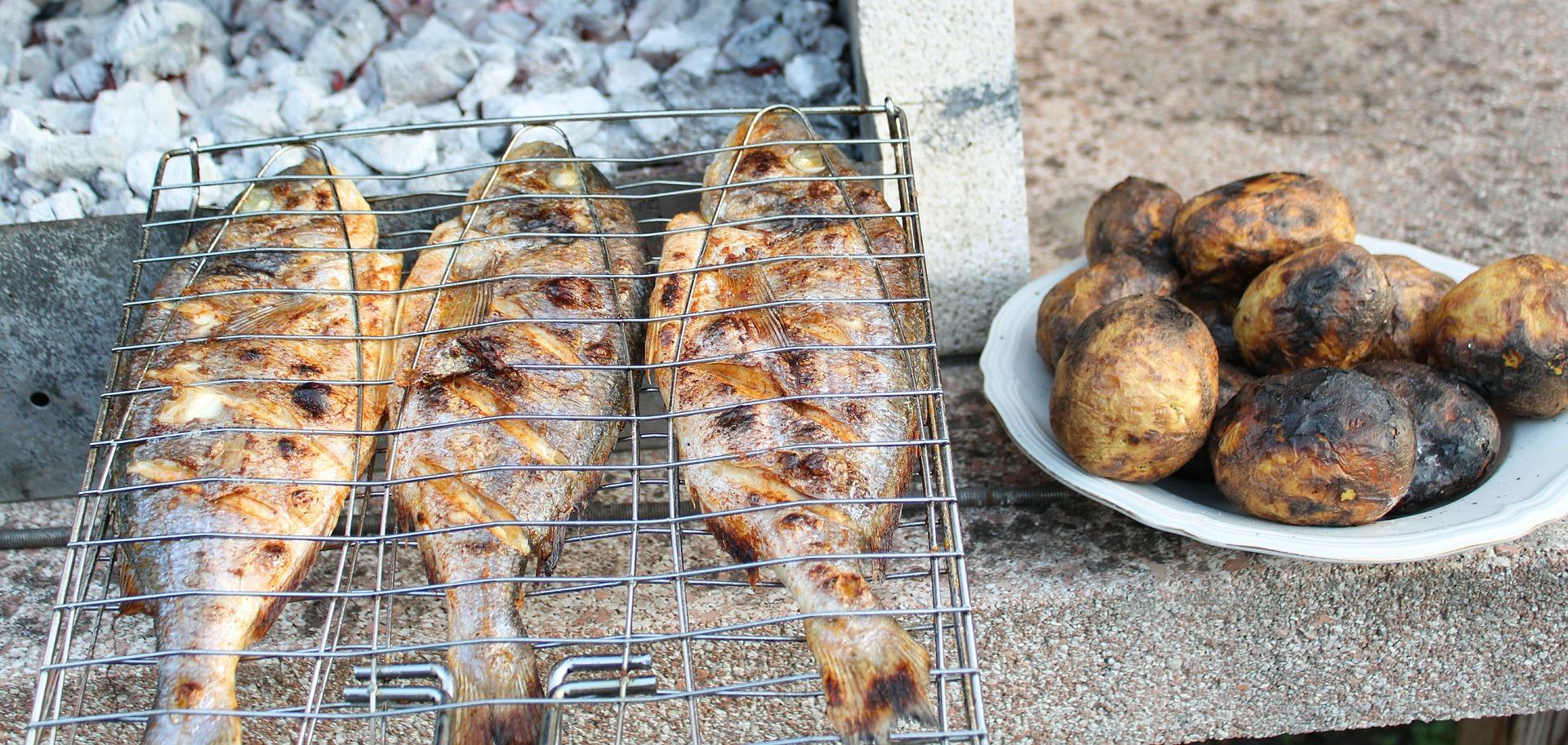 Uma grelha para peixe com três sardinha em cima de uma mesa de pedra. Ao lado existe um prato branco com batatas cozidas.