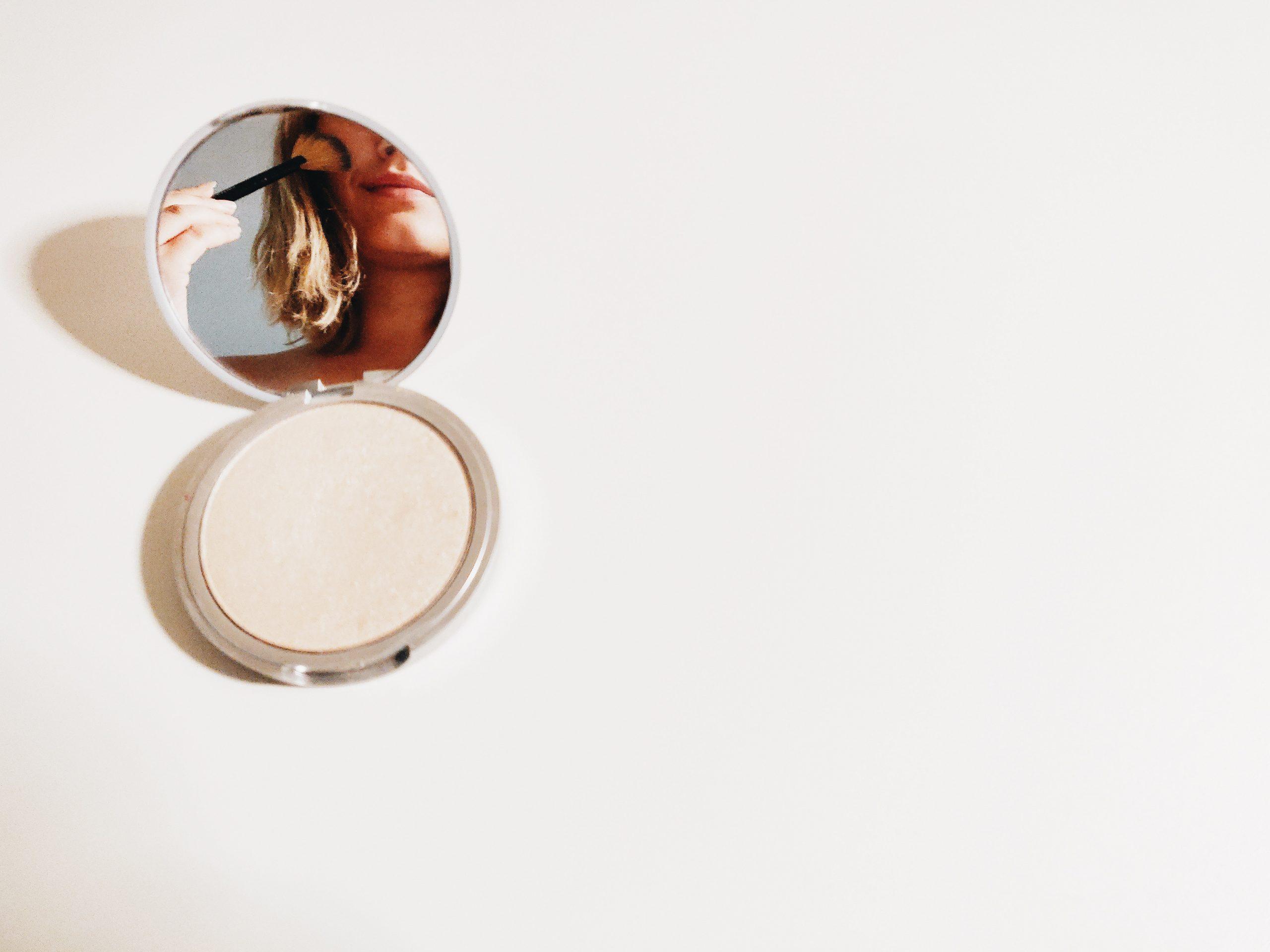 Foto de um pó iluminador aberto, com seu espelho refletindo uma mulher aplicando o iluminador com um pinel.