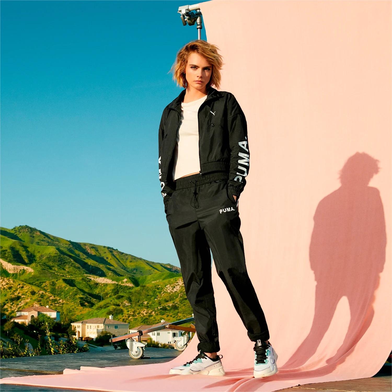 Modelo posa com jaqueta Puma em fundo rosa com morros ao fundo