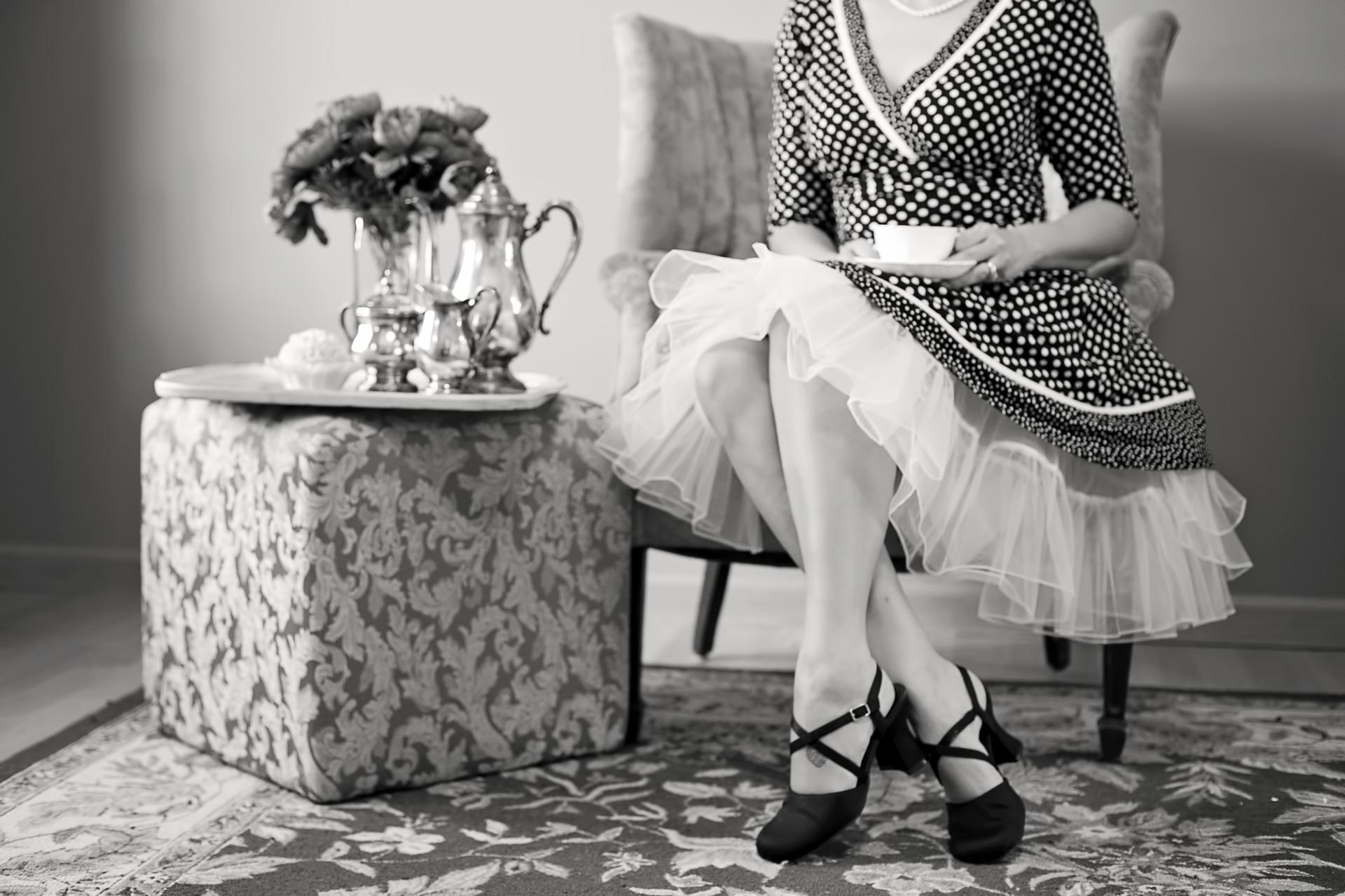 Imagem preto e branco de mulher sentada em cadeira, segurando uma xícara com jogo de chá de prata ao lado