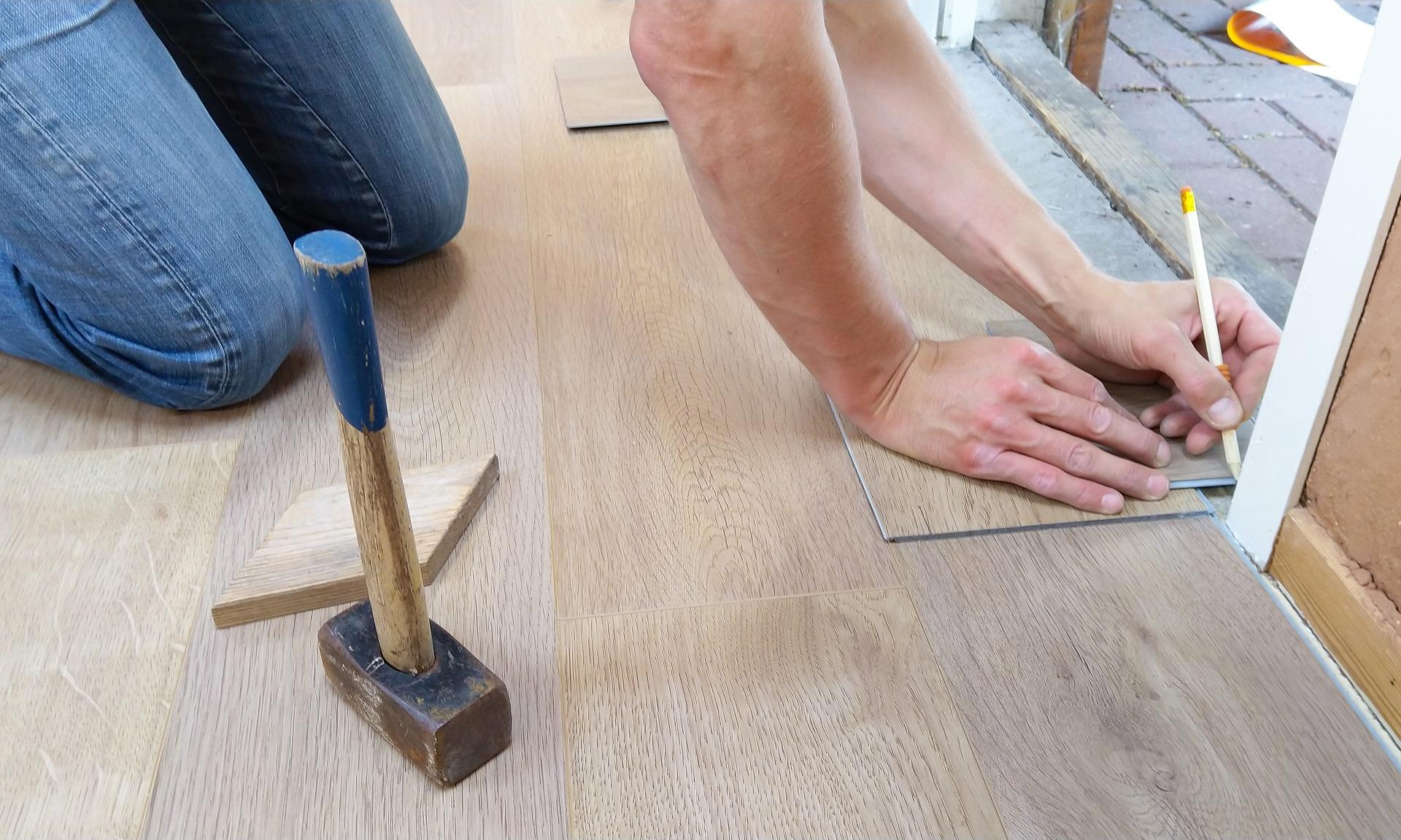 Uma mão masculina segurando um lápis para carpinteiro sendo utilizado para riscar uma parede e a outra mão segurando um pedaço de piso de madeira.