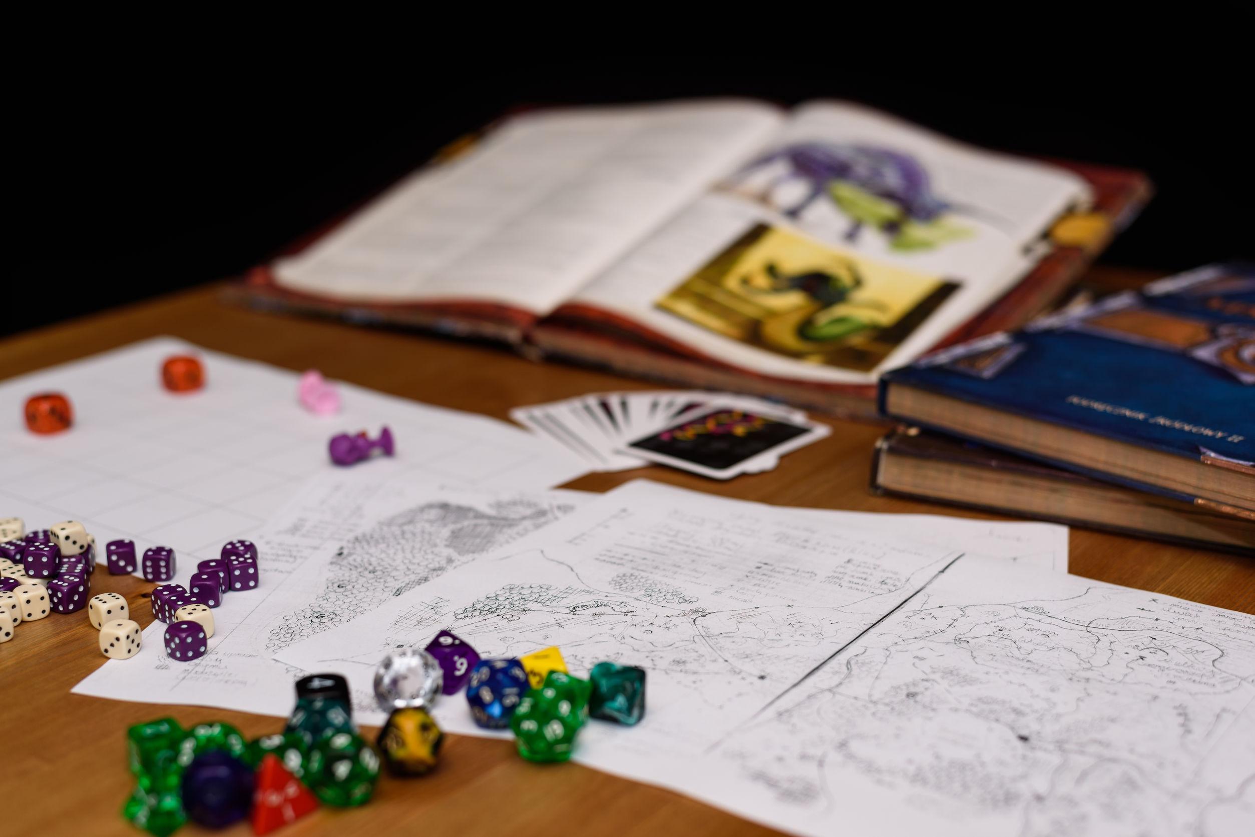 Dados de RPG, fichas de personagens e alguns livros de RPG sobre uma mesa.