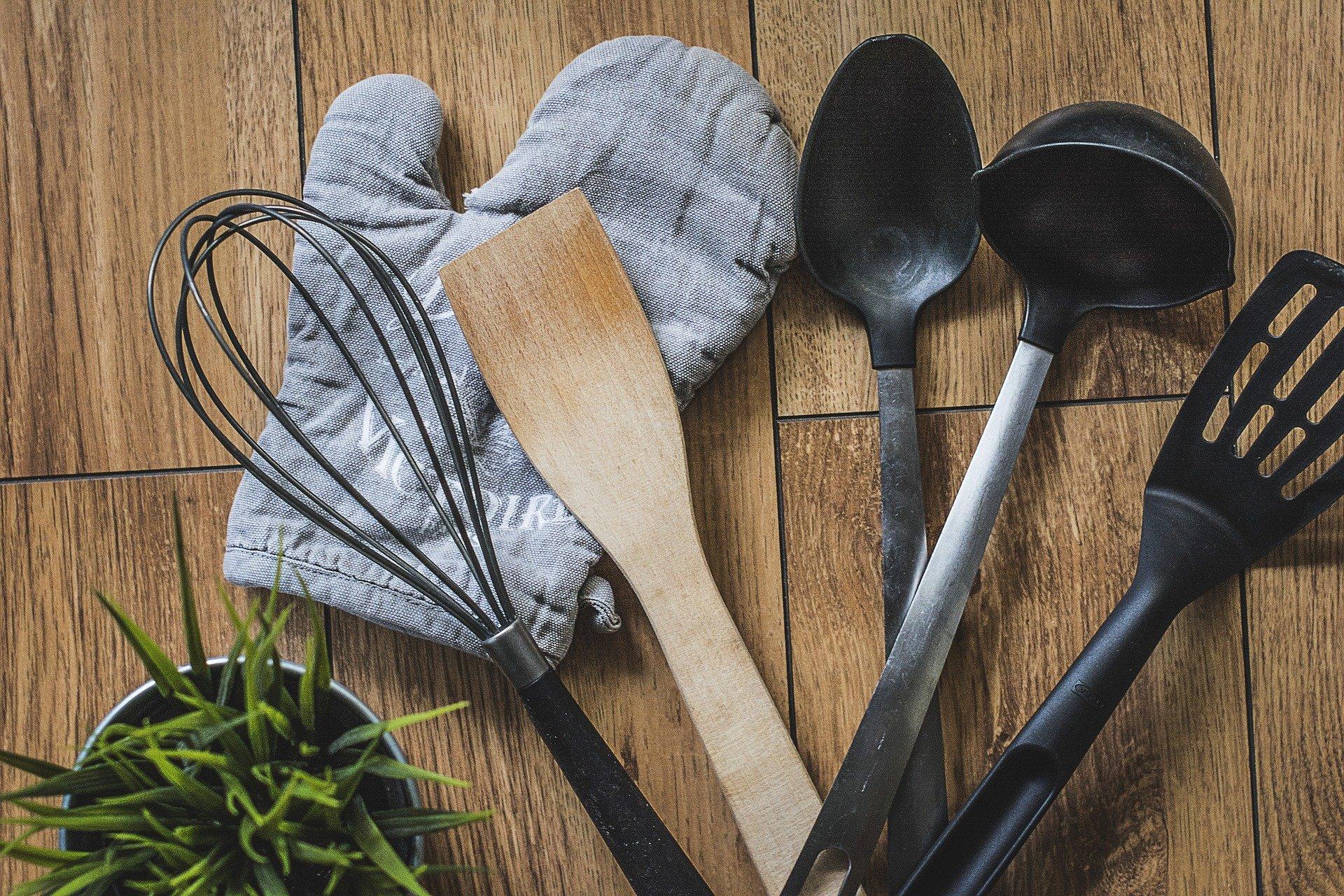 Foto de uma luva de cozinha em cima de um balcão, acompanhada de algumas colher e utensílios domésticos, além de um vaso de planta.