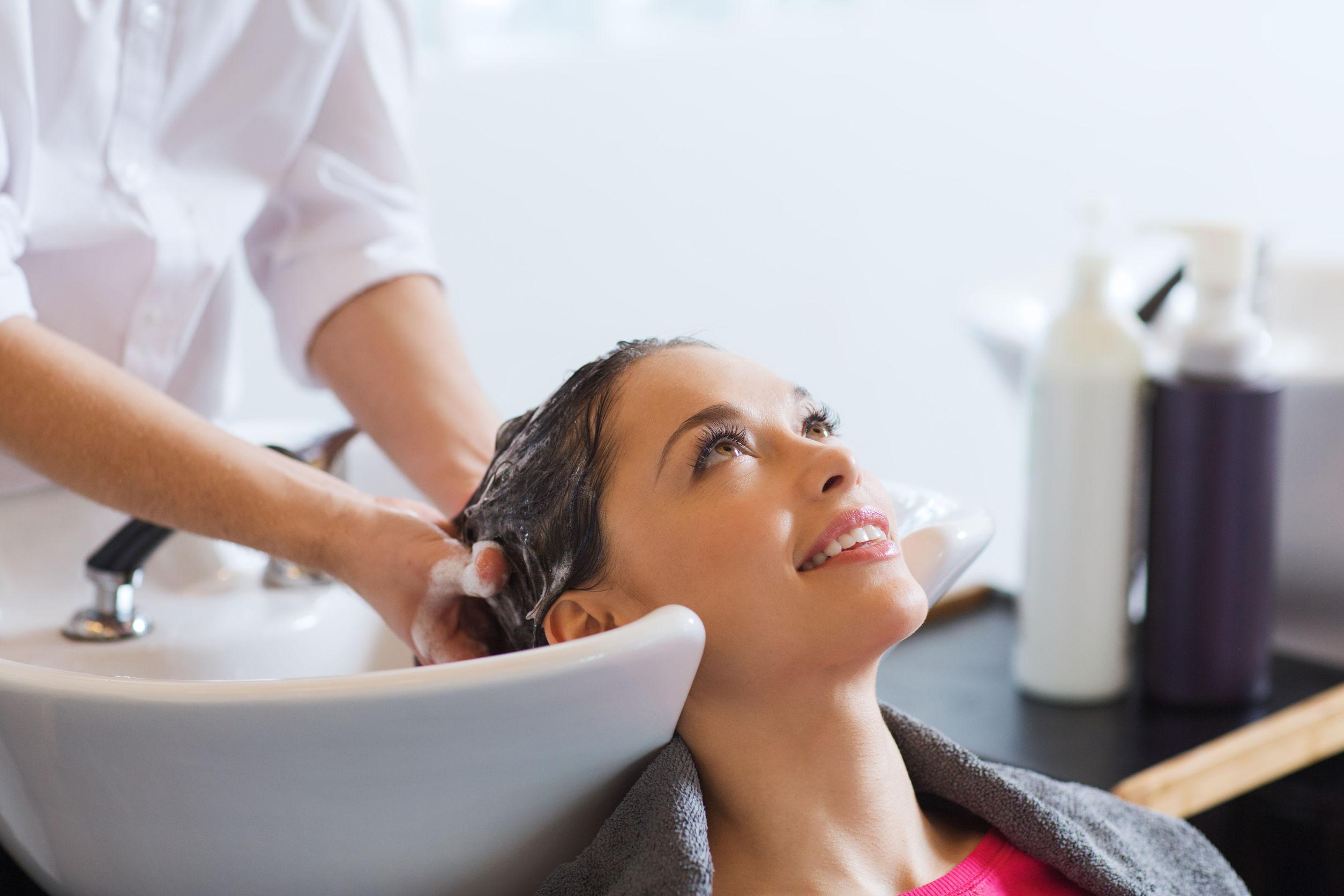 Foto de uma mulher em um lavatório de salão de beleza, tendo seus cabelo lavados e hidratados por uma outra pessoa. A mulher está sorridente e olhando pra cima. Ao fundo, cremes de hidratação.