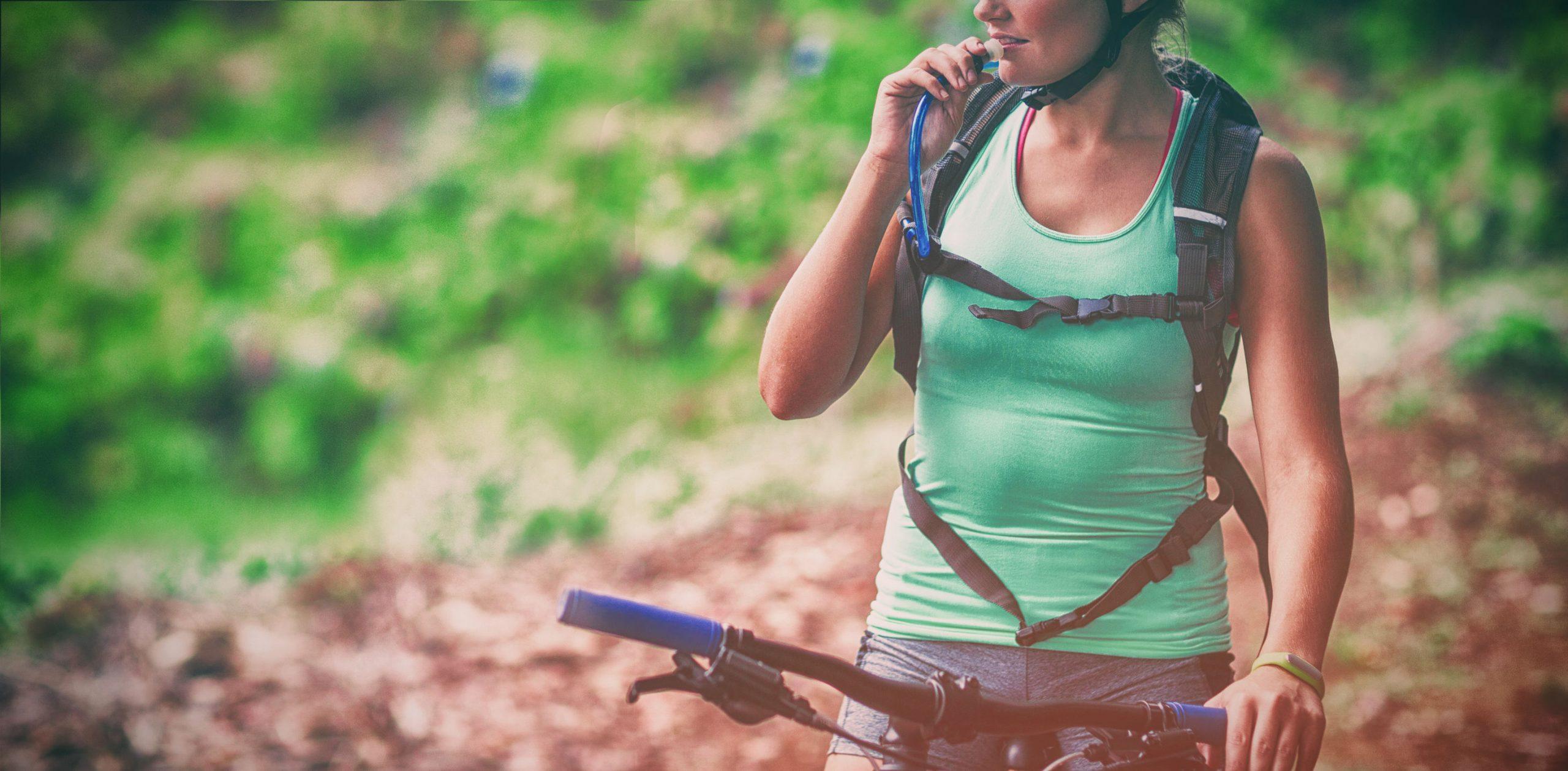 Imagem de mulher andando de bicicleta e bebendo água de uma mochila de hidratação