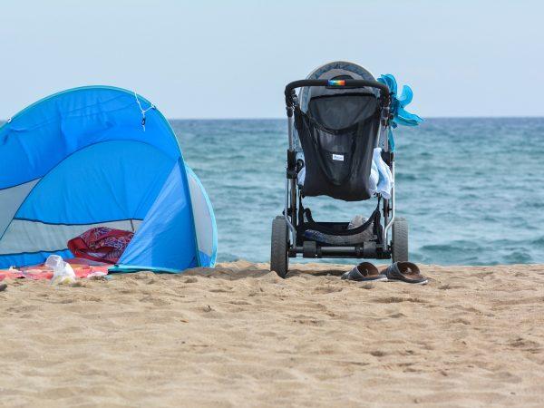 Imagem de carrinho com mosquiteiro em praia ao lado de barraca azul