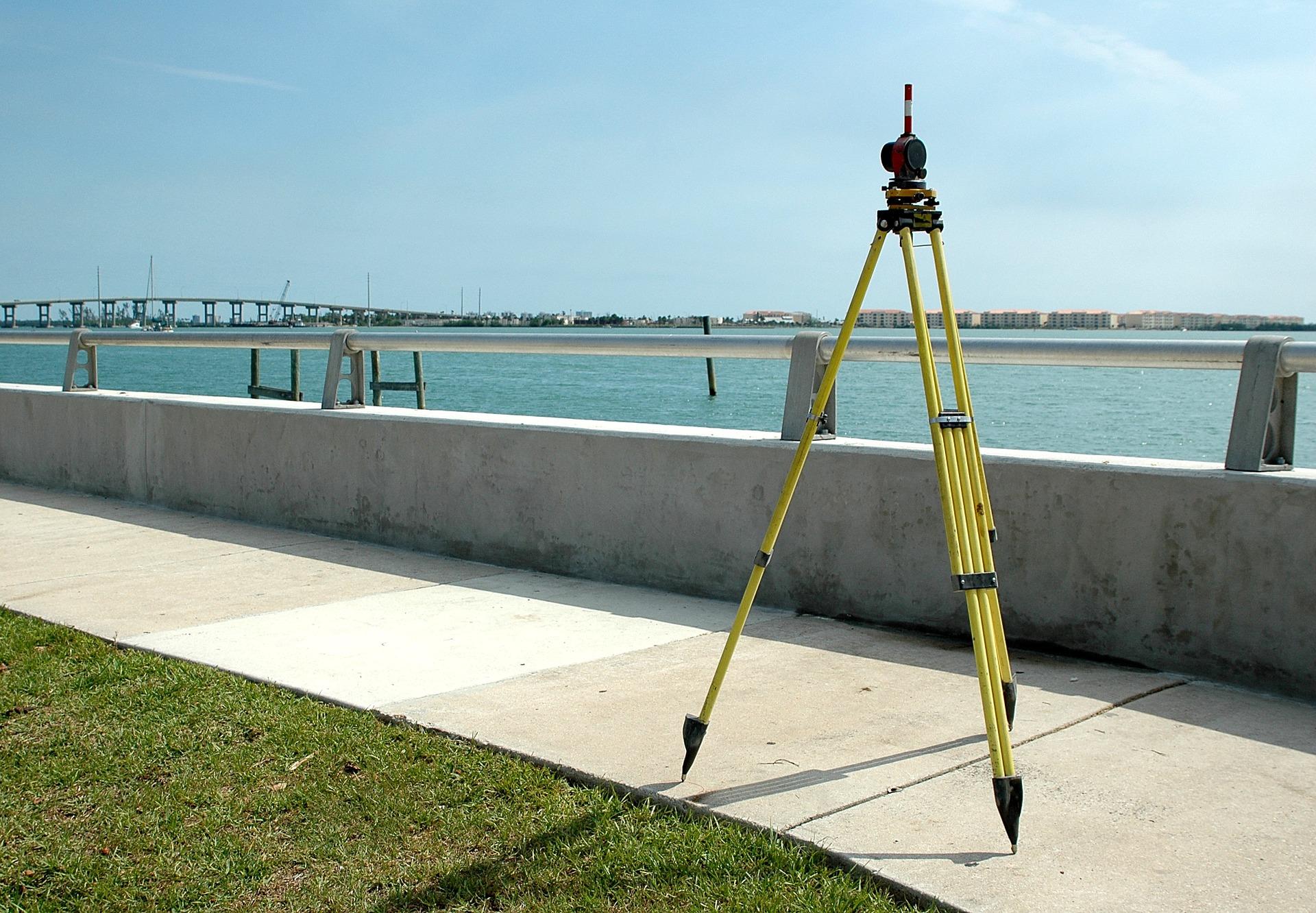 Um nível a laser em um tripé medindo uma área de concreto próxima a uma represa.