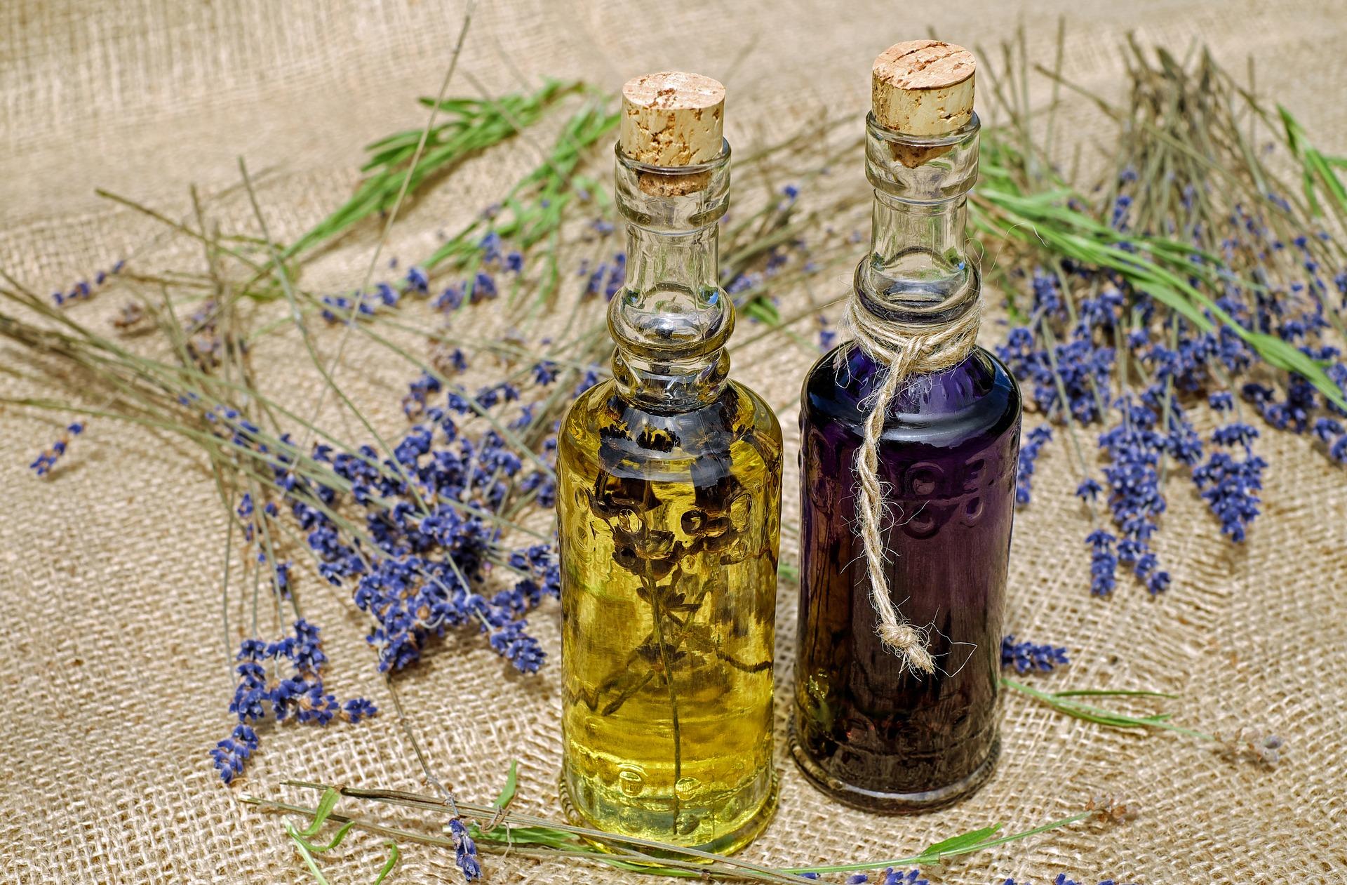 Foto de dois frasquinhos de vidro com óleos dentro, sendo um claro e o outro escuro. Ao redor, várias flores de lavanda.
