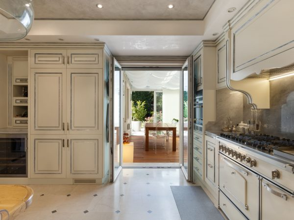 Foto de uma cozinha clássica com estilo provençal, móveis e piso claros. Nela há diversos armários, dentro eles um paneleiro, um fogão, uma pequena adega, além de uma porta aberta que dá para outro cômodo.