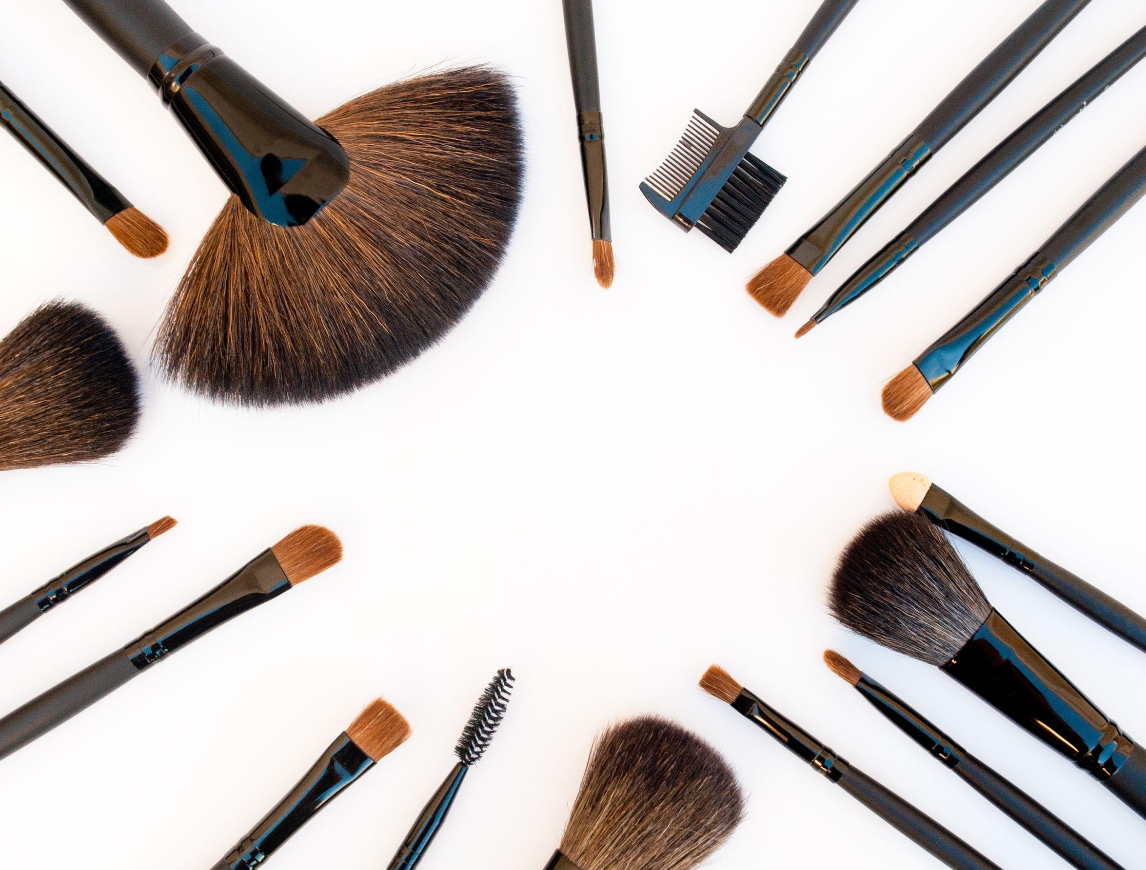 Foto de vários pinceis de maquiagem juntos, todos com cabo preto. Entre eles, o pincel leque.