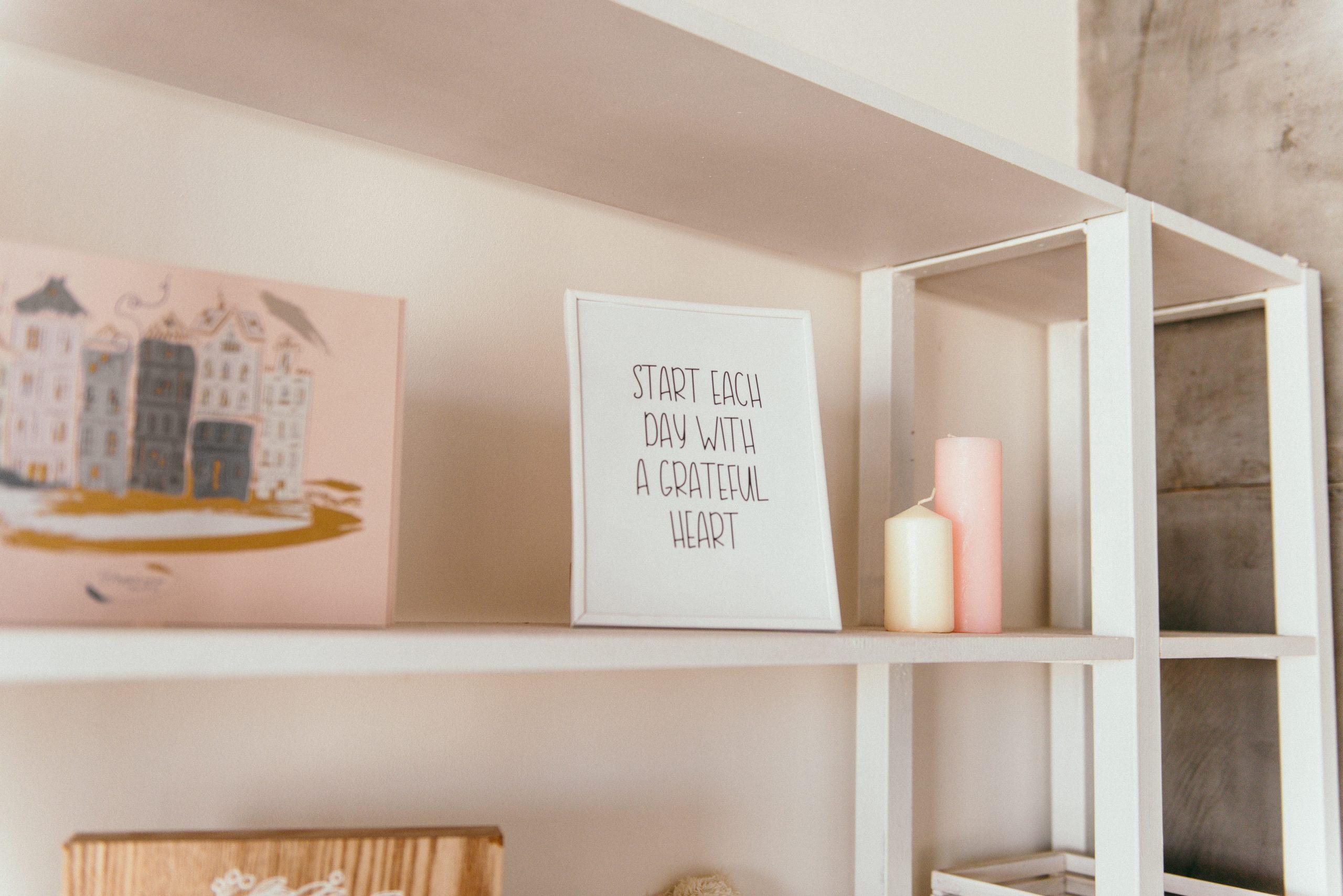 Imagem de porta-retratos branco com frase de incentivo sobre estante ao lado de velas coloridas