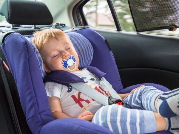 Um protetor solar para carro no vidro e um bebê dormindo no banco de trás do carro