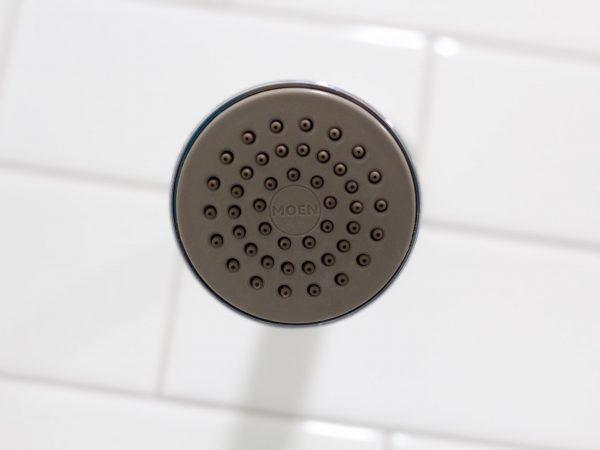 A parte de baixo de um chuveiro instalado no banheiro com azulejo branco no teto.