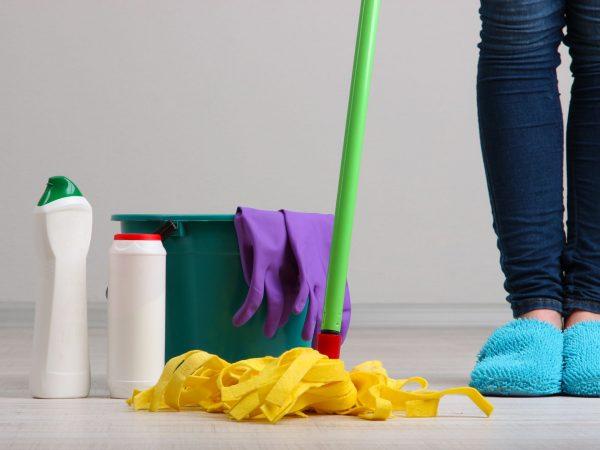 imagem cortada mostra mulher de pantufa segurando rodo e com materiais de limpeza ao lado