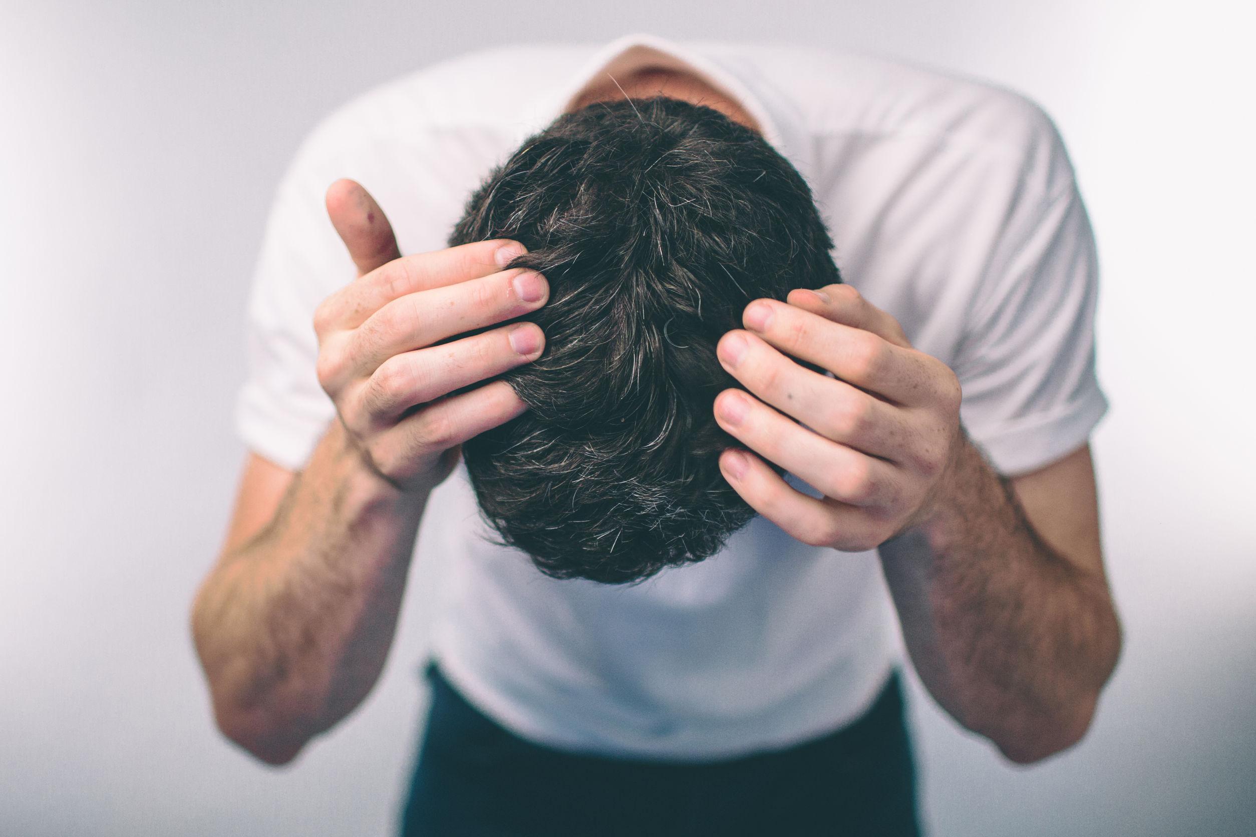 Foto de um homem de camiseta branca, inclinado para frente, sem mostrar o rosto, com as mãos no cabelo.