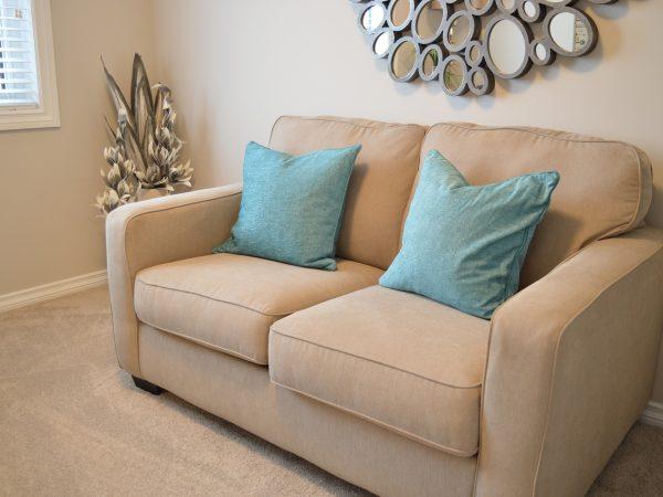 Imagem de sofá 2 lugares bege com duas almofadas azuis