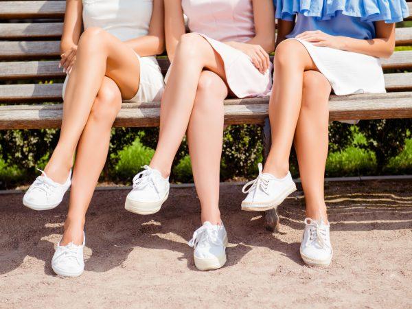 Foto de três meninas sentadas, todas de pernas cruzadas, vestindo saias brancas e tênis também brancos.