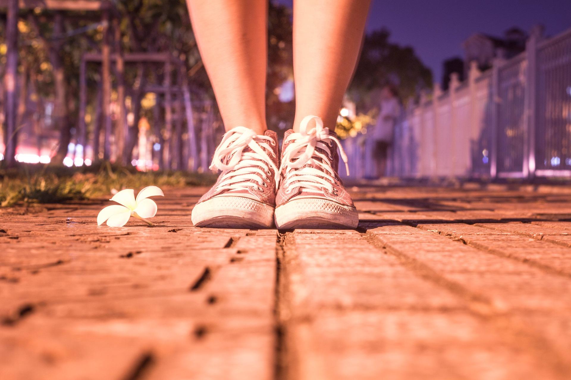 Imagem dos pés de uma moça com um tênis rosa em cima de um tronco de árvore