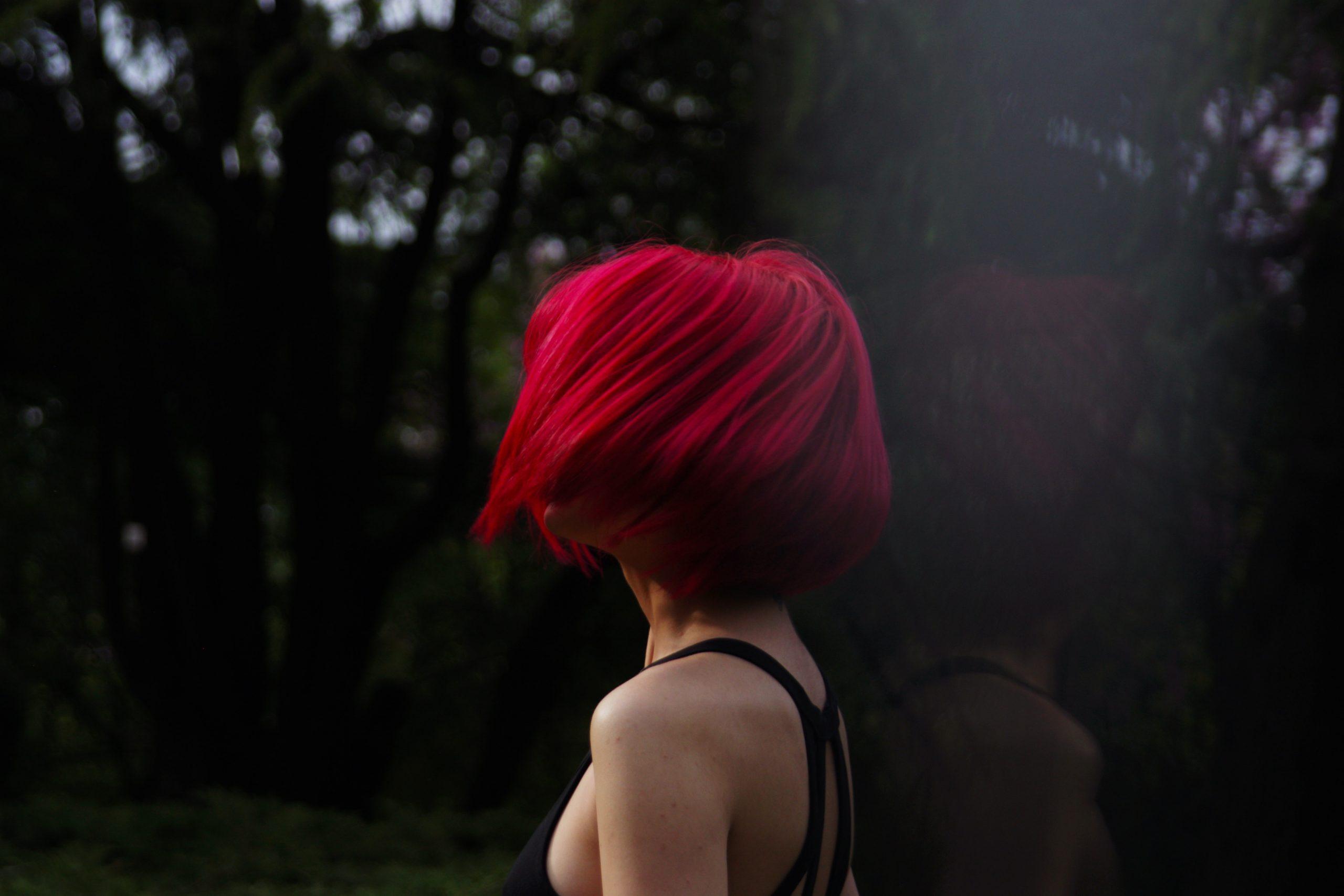 Foto de uma mulher de lado, jogando o cabelo chanel, tingido de vermelho, para o lado. Ao fundo, várias árvores.