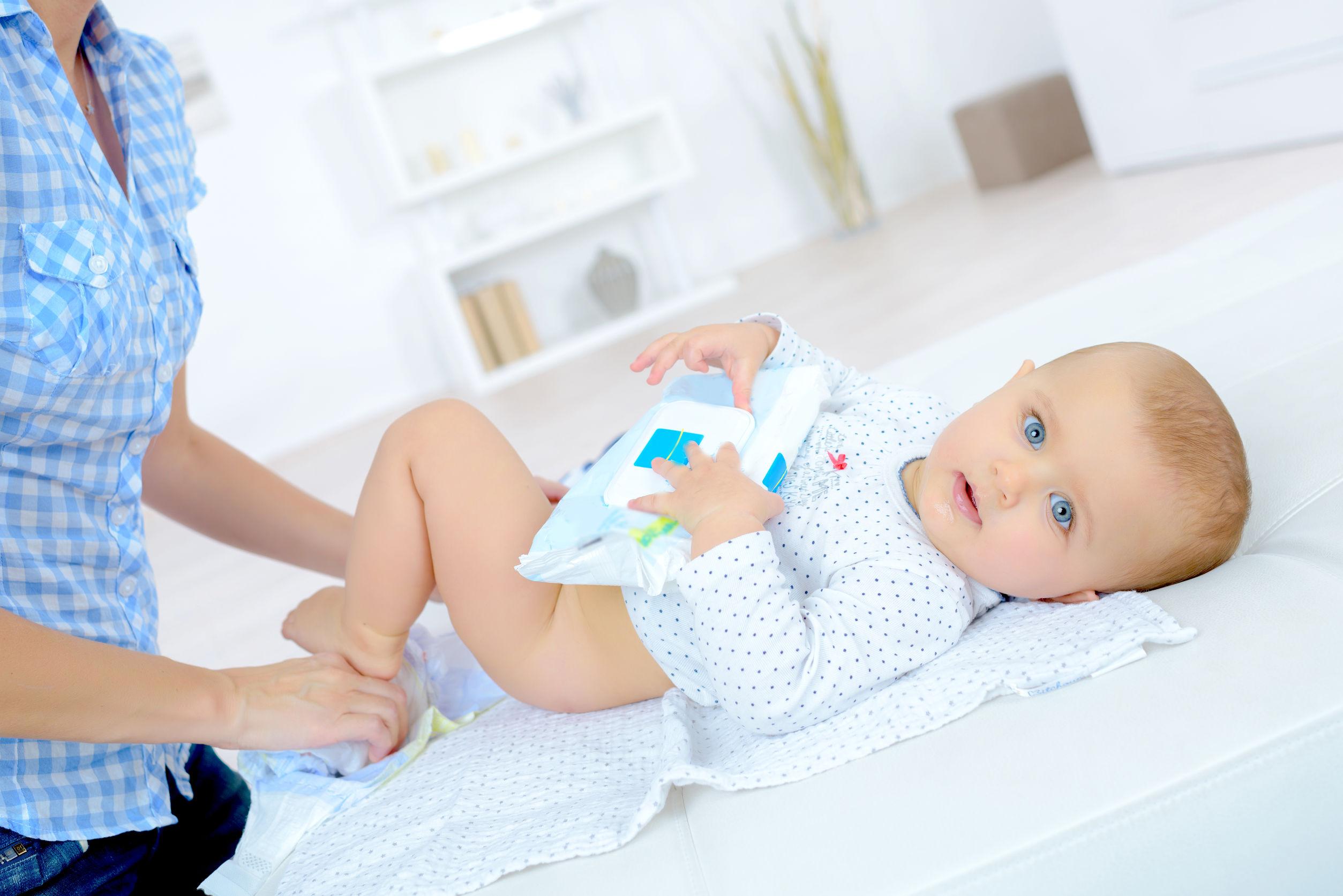 Imagem de uma mulher trocando a fralda de um bebê em uma superfície branca