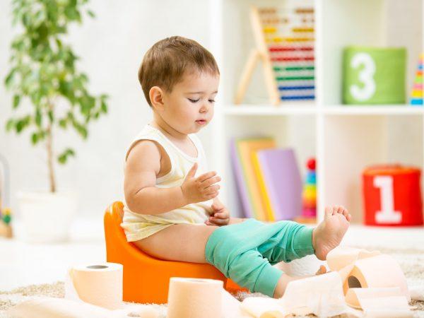 Imagem de criança sentada em troninho laranja cercada de rolos de papel higiênico