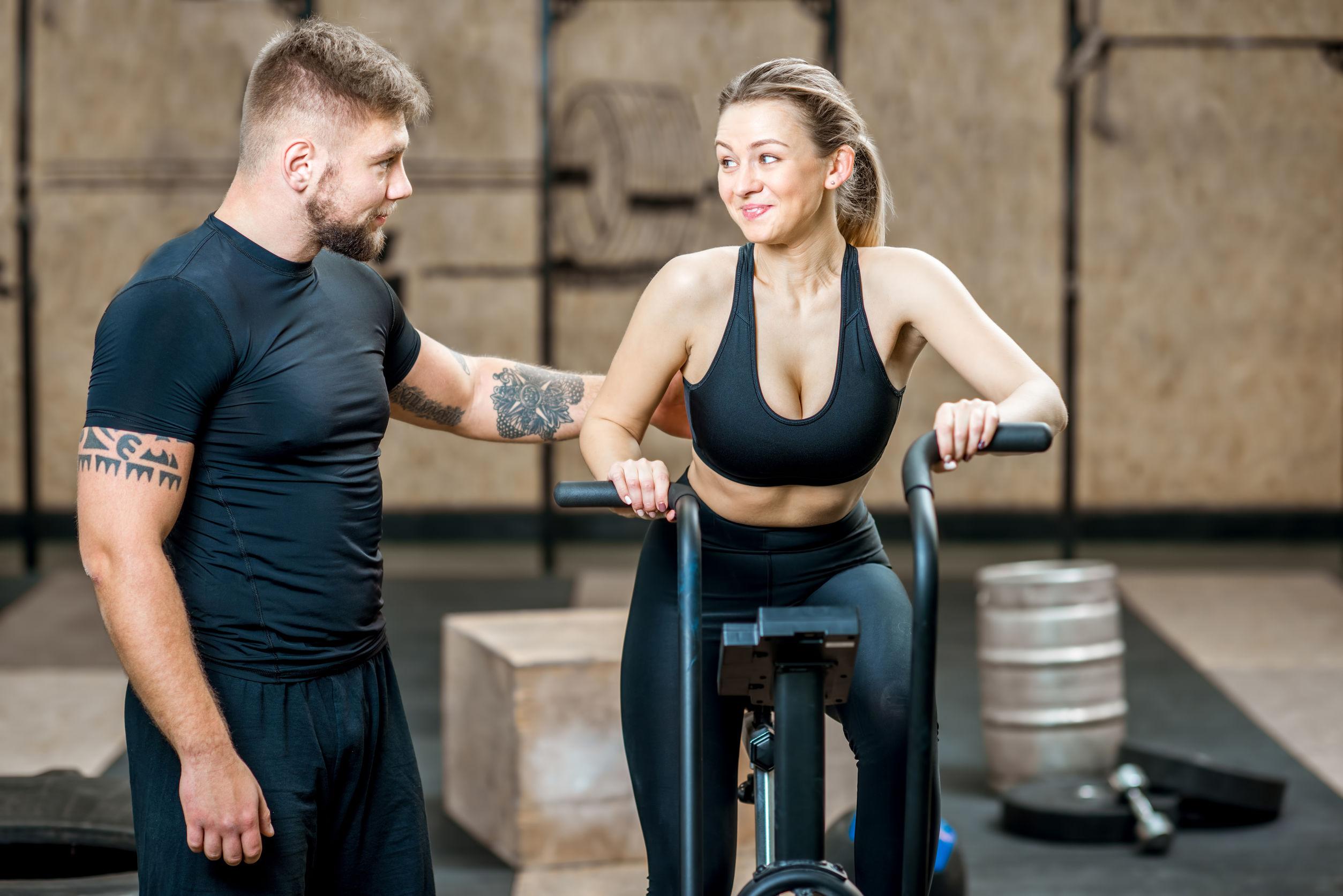 Imagem mostra um homem ao lado de uma mulher que pratica airbike.