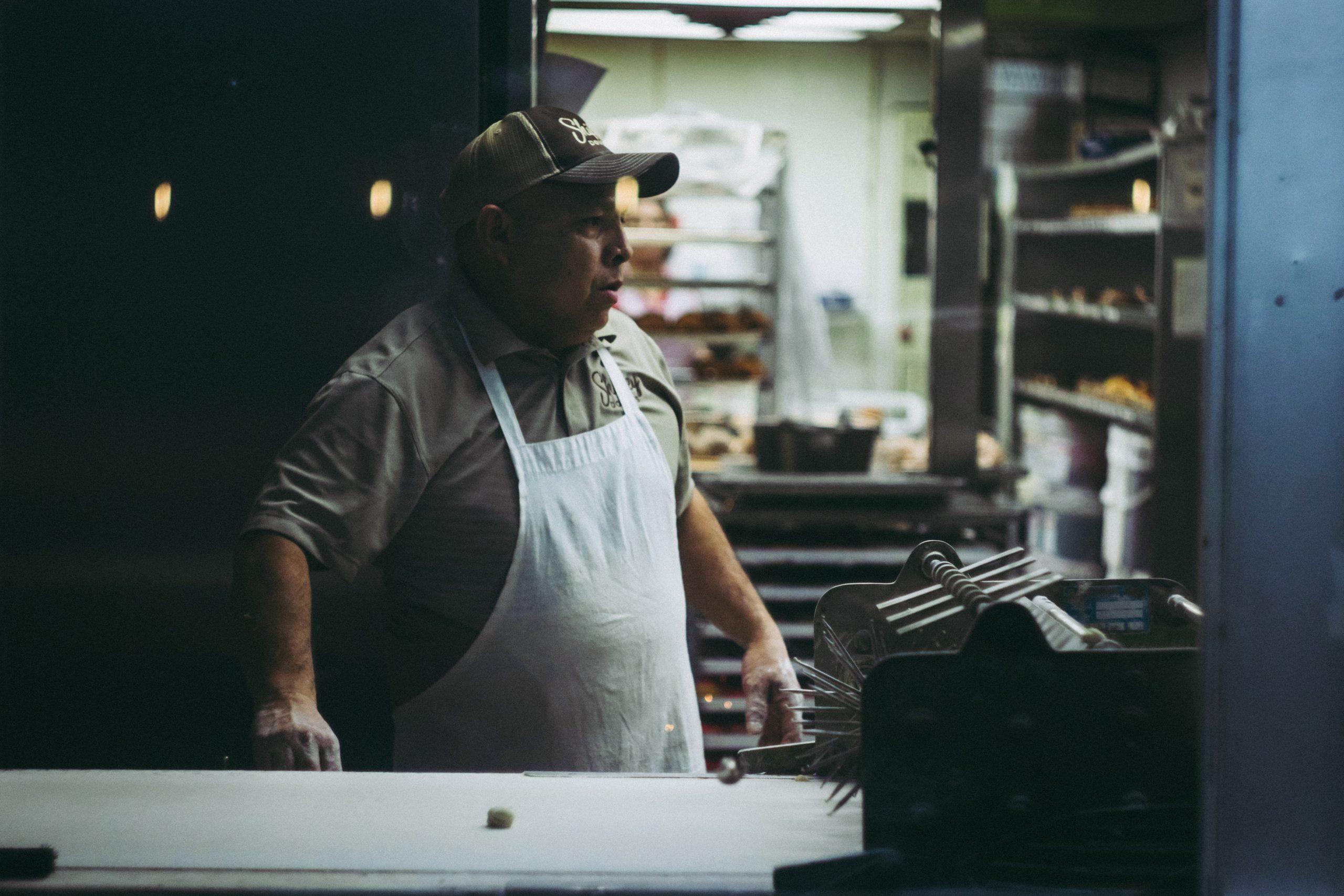 Foto de um homem olhando para o lado, de avental branco e boné, trabalhando em uma cozinha de padaria.