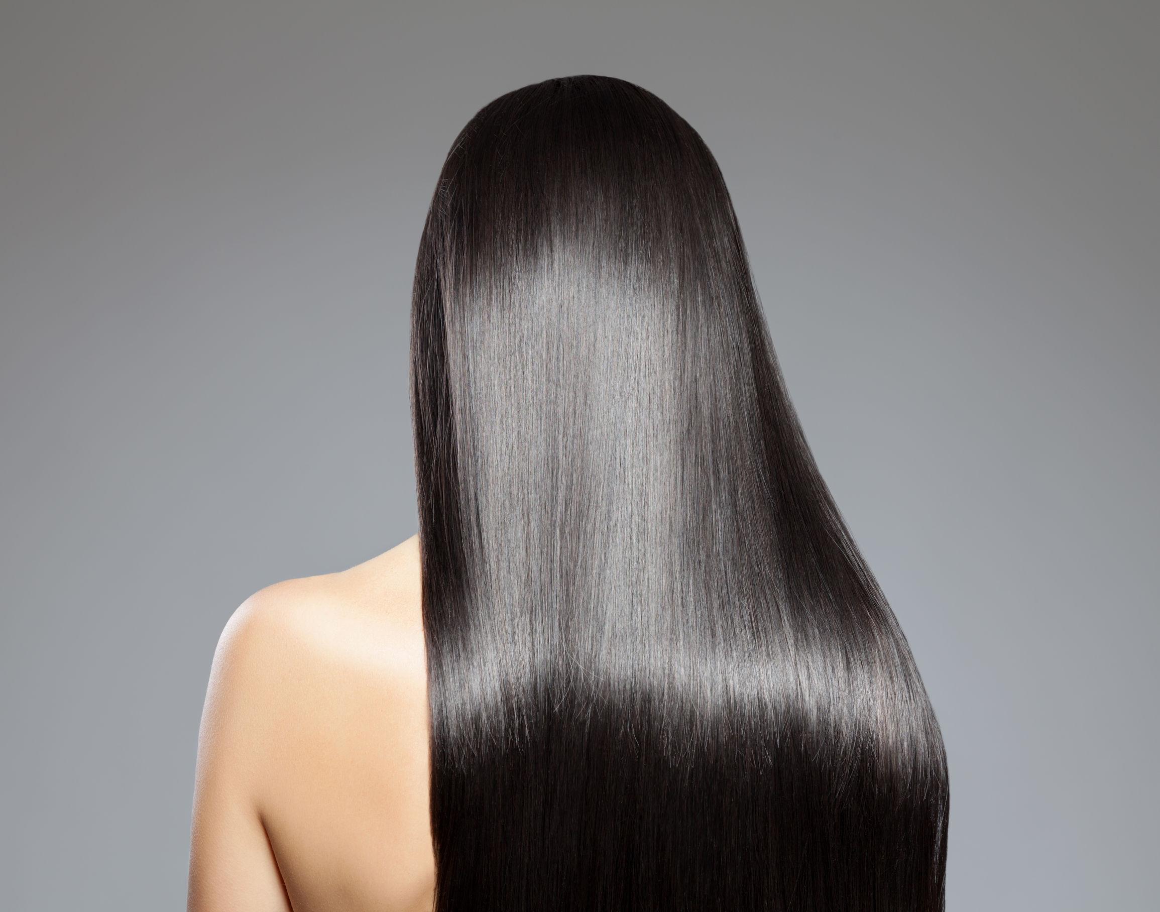 Mulher com cabelo longo preto liso brilhoso de costas.
