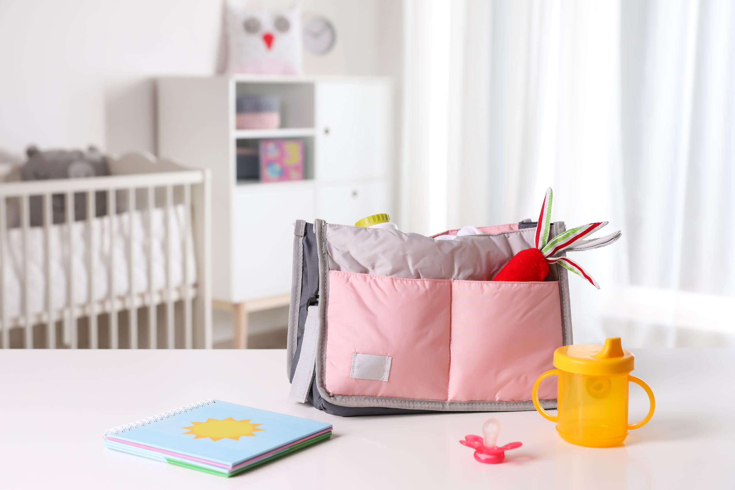 Bolsa de bebê sobre bancada em quarto do bebê.