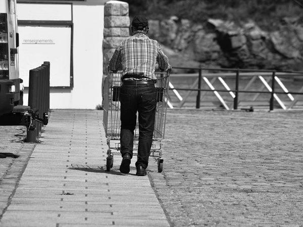Imagem preto e branco de homem empurrando carrinho de compra vazio por estacionamento
