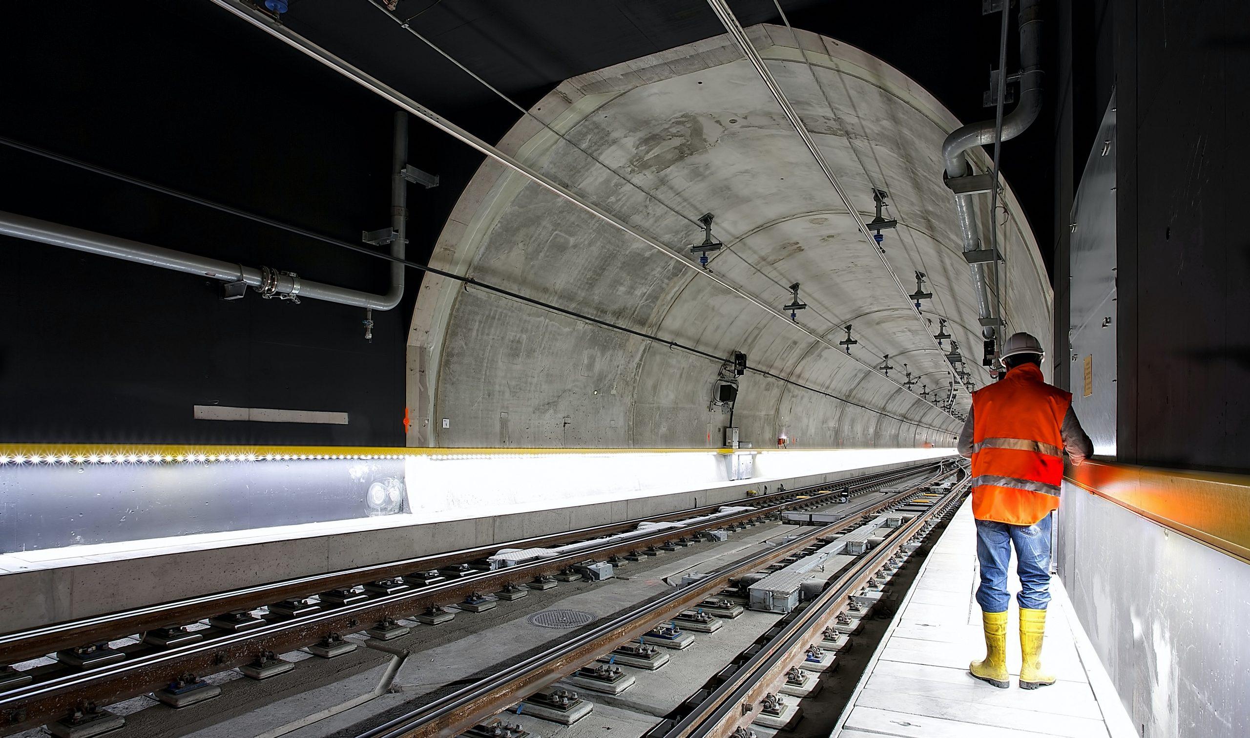 Imagem mostra um homem usando um colete refletivo ao lado de uma linha de trem.