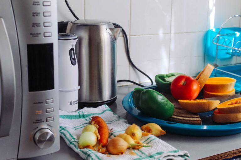 Cafeteira, blender e microondas com alimentos.