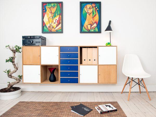 Foto de um ambiente de uma sala, com estantes fixadas na parede, uma cadeira com assento branco, uma planta, um tapete com livros em cima, dois quadros coloridos, um abajur e um toca discos.