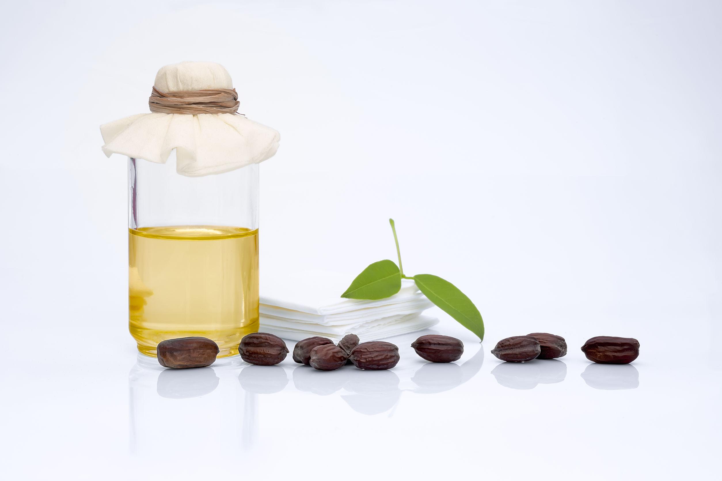 Foto de um vidro com óleo de jojoba, ao lado de grãos de jojoba, folhas e o que parecem ser toalhinhas brancas.