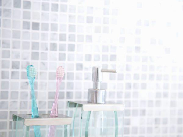 Porrta escovas com duas escovas de dente ao lado de porta sabonete líquido